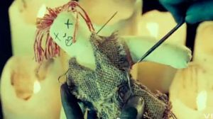 Image of 'voodoo doll' and painted black hands in Florence + the Machine video. Via Jezebel
