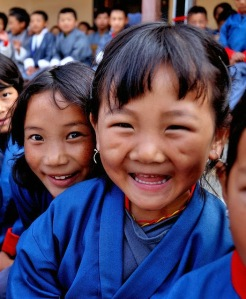 Bhutanese girls crowd in front of the camera, smiling broadly