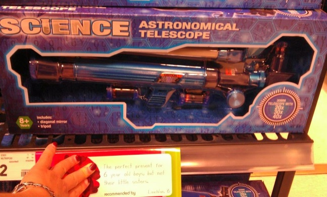 Toy astronomical telescope with a handwritten sign saying it's best suited for a boy. My hand holds the sign down