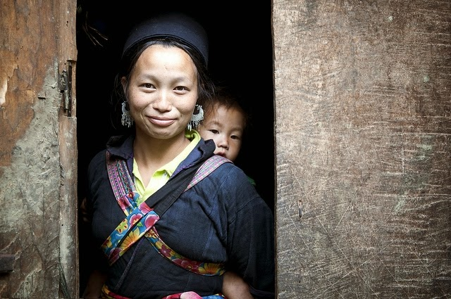 A woman smiles in a doorway. She carries her small child on her back