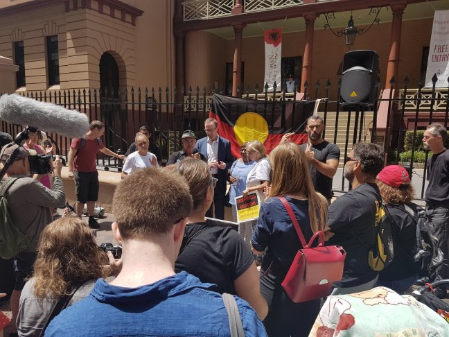 Protesters gather out the front of the Parliament of New South Wales. A lage Aboriginal flag hangs over the gates. An Aboriginal man is signing translation in Auslan. There are camera crews and photographers.