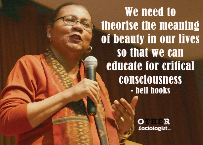 bell hooks speaks into a microphone. She wears glasses, an orange top and beautiful matching orange scarf