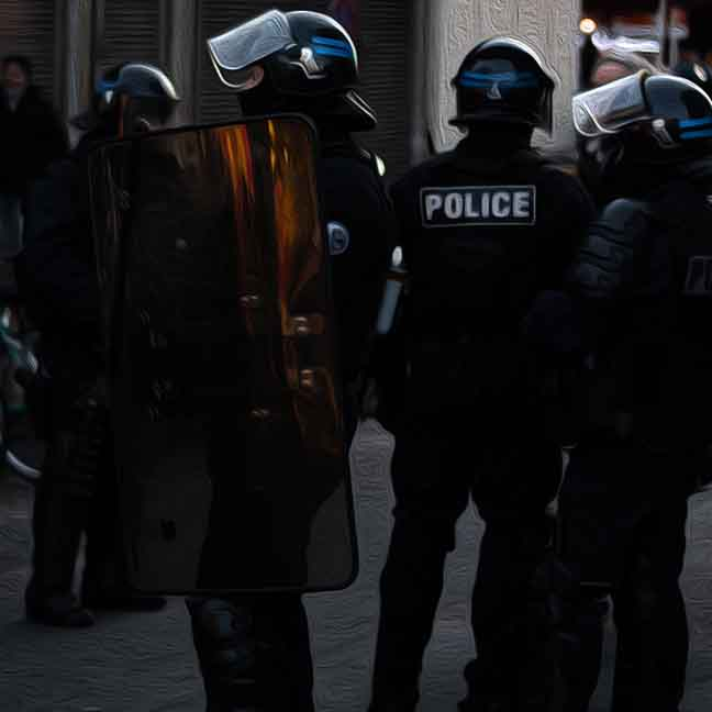 Police in riot gear stand outdoors