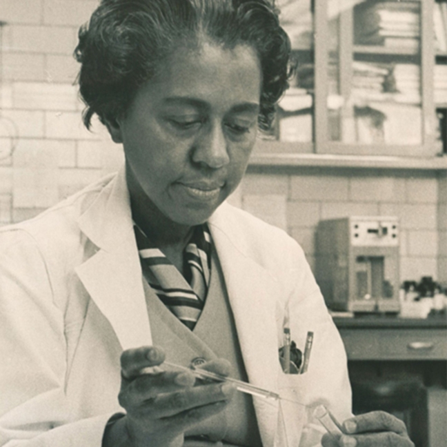 Black and white photo of Dr Marie Maynard Daly in a lab. She is pouring liquid into a beaker and she wears a lab coat