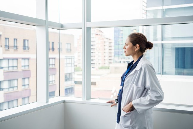 An Aboriginal woman in a white lab coat, staring out the window of an office