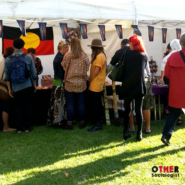 People at a stall on Survival Day event, with an Aboriginal flag in the background
