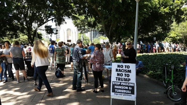 """No to racism"" standing sign in the foreground with people walking in the background"