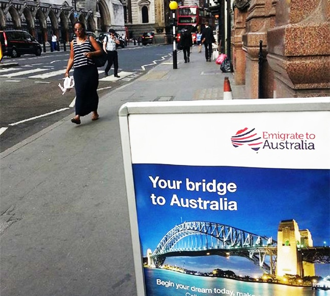 In London, emigrate to Australia sign is in the foreground, and people walk in the background