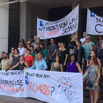People stand in front of pro-choice banners outside Northern Territory Parliament