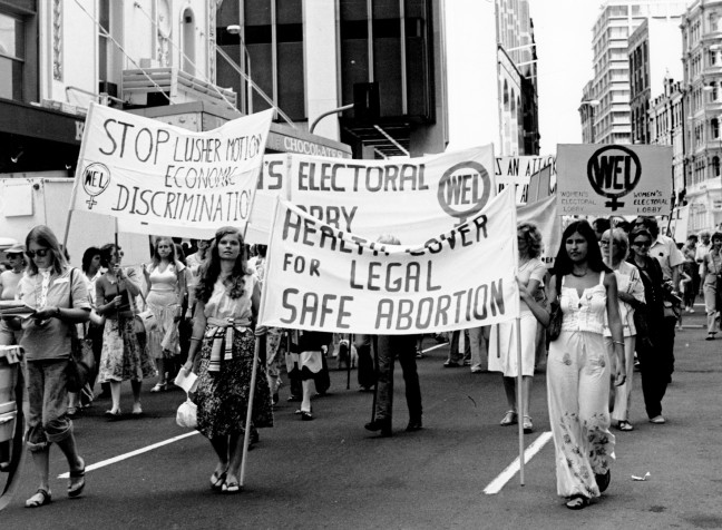 Women march through the city of Sydney behind large pro-choice banners