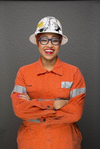 Yassmin Abdel-Magied wearing a construction hat and orange clothing denoting oil rig gear