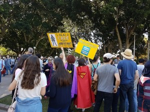 Protesters gathered in Hyde Park, Sydney. Two women are dressed in capes. They are holding yellow signs. One says
