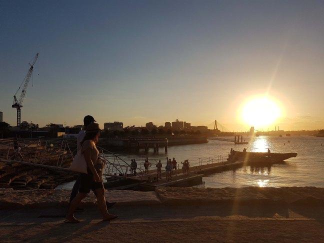 两个人沿着海滨散步。在背景中,其他小组聚集在码头拍照和环顾四周,而其他小组则在一艘巨轮附近。太阳落在水面上时发出明亮的光