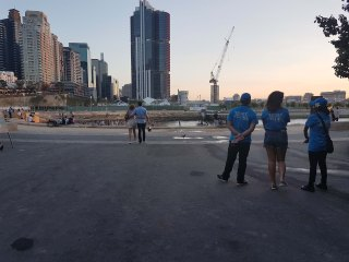 Tree Sydney Festival volunteers stand together to the left hand side, a couple can be seen with their arms around each other walking in the background. The Barangaroo foreshore is seen in the far disance with buildings towering over the top