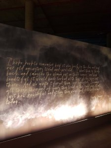 Mural with fish on the top right hand side drawn, with cursive writing that reads: I hope people remember how it was back in the day and how our old ancestors lived and survived. I want them to think back and imagine the women out on their canoes and how beautiful it would have looked with their fires going out there. And we mustn't forget them, our acncestors. Because all those thousand of years they lived on this land says it alll. Just how powerful and strong they were, and still surviving today. - Phillis Stewart