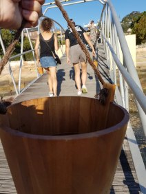 Close-up of my wooden bucket. Part of my hand is seen at the top of the photo, and other people walk across a bridge in the background. It is a sunny day