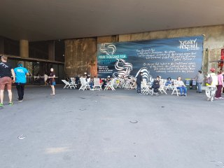 "The exterior of Barangaroo undercover area. In the background is a giant mural with the Sydney Festival logo and the title ""Four Thousand Fish."" Information about the exhibition can be seen in cursive writing but cannot be easily read from a distance. People sit on white deck chairs, while others walk in either direction"