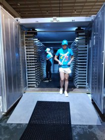 A young person looks down as they walk out of a giant portable freezer. In the background a woman stands in the middle of metal racks, awaiting the ice fish