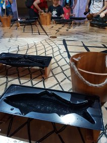 Part of a round table can be seen with black drawing imitating fishing lines. On top sits my wooden bucket and fish mould. In the background, children and adults look down at their own frozen fish