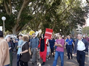 People march across Hyde Park, Sydney. A man dressed in a furry black and red onesie suit holds a red sign that reads: Heed our warning signals