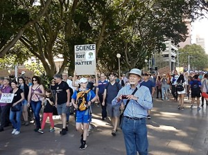 March for Science protesters in Hyde Park, Sydney. An older White man is in the foreground. Behind him someone holds a sign that reads
