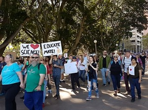 March for Science protesters walk through Hyde Park, Sydney. A White, bearded man wears a bright green t-shirt in the front. Behind him one person holds a sign