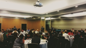 Workshop participants in a large conference room. They sit at tables in small groups, looking down at their paperwork