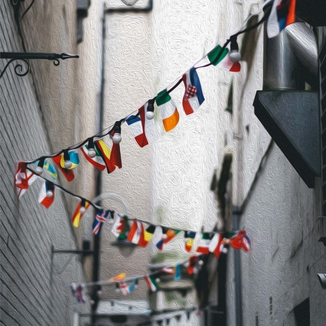 Flags from around the world hang high above an alleyway