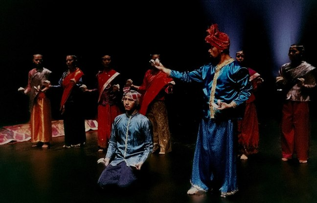 A male dancer in the centre kneels, another male dancer in blue stands with an outstretched arm, while women danders stand in the background