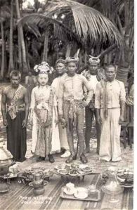 Tausug people stand togeher in traditional costume. Men and women wear apnts and fabric belts and ornate crowns