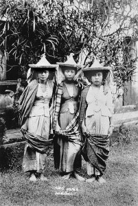 Three women stand together. They wear pointed hats, fitted vests, billowy pants and long fabric wrapped around their backs and scross their lower legs