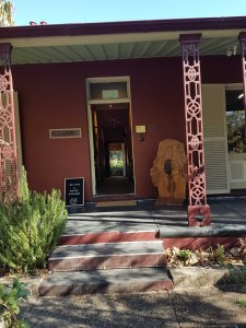 The front door has beautiful Aboriginal artworks and woodwork and a green shrub
