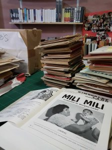 A stack of books and periodicals are shown on a table, with the black and white magazine, Mili Mili, in the foreground. The cover has an Aboriginal woman holding a baby up in the air