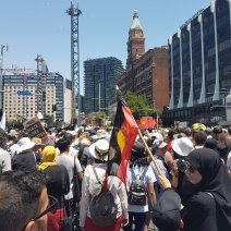 Invasion Day - Muslim woman holds Aboriginal flag
