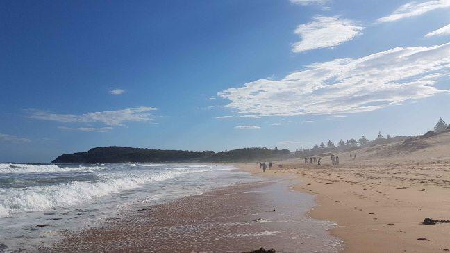Beautiful clear beach on a clear day.人们走在后面