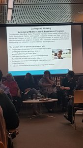 Panellists sit in the front of the room with a PowerPoint slide projected behind them. The slide shows an Aboriginal woman holding a baby. The text is hard to read without zooming, but it describes the program and aims