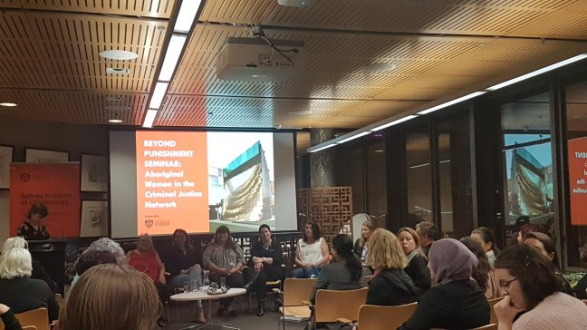 A room full of majority women watch a mix of Aboriginal and non-Indigenous women panellists at the Sydney Law School