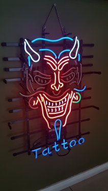 "Neon sign of a devil creature with horns and a moustache, says ""Tattoo"" at the bottom"