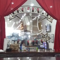"Frosted glass with ""Broadway Tattoo"" sign drawn across thhe centre and a drawing of a top hat. Framed by red curtains"