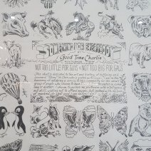 Black and white poster behind glass wth various drawings around the edges, showing animals, skulls, flowers, flags and hearts. In the centre is writing, mostly hard to read. Notably it says: Something For Everybody, by Good Time Charlie.Broadway Tattoo, Sydney