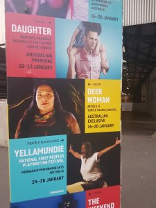 Large set of posters at Carriageworks shows various shows at the Syndey Festival. A large space can be seen in the background