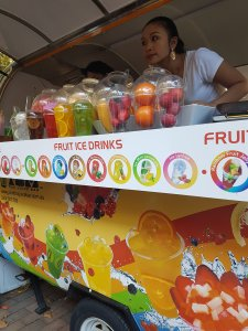 Bright coloured van displays fruits and juices. The sign says: Fruit Ice Drinks. An Asian woman leans forward inside a campervan portable shop, listening intently to an order