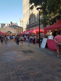 红色的天篷遮蔽了岩石上的多个市场摊位,悉尼。人们穿着短裤和夏装走路