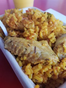 Delicious yellow rice with chicken sits on a pink table with orange juice in the background