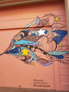 Street art against a salmon door. A beautiful blue, purple, yellow and black cosmic scene shows dogs, stars and other non-descriptfigures