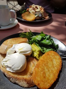 Close-up of a breakfast feast, including sour dough, poached eggs, spinach and avocado with a hashbrown. Another breakfast of eggs Benedict can be seen in the background