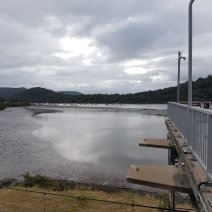 Water scence with grey skies. The side of the Hawkesbury Train Station can be seen