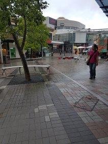 一位亚洲妇女正在户外霍恩斯比购物中心的一棵树旁散步,她身后有五颜六色的货车和商店