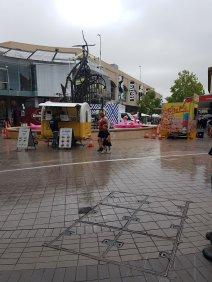 一个女人和一个女孩穿着夏装,在雨中走过两辆食品车