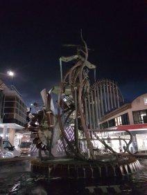 晚上,霍恩斯比。一座巨大的金属雕像和喷泉看起来很奇怪,有水磨和水管